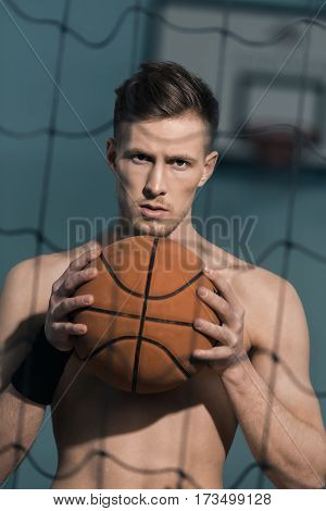 portrait of confident sporty man holding basketball ball