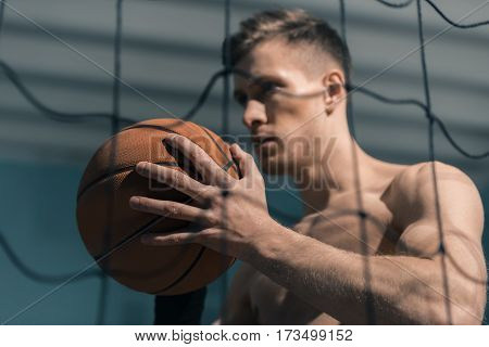 side view of sporty man holding basketball ball in hands