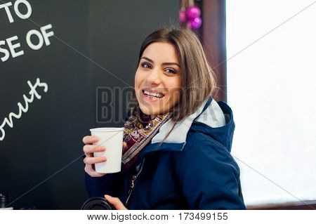 Girl holding a to go cup of coffee in a coffee shop, enjoying the flavor smiling and looking at camera.