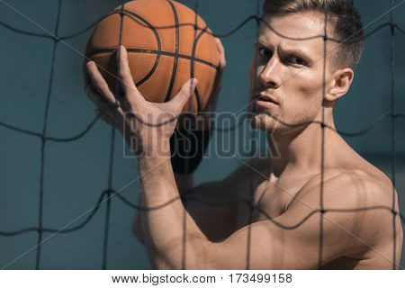 portrait of concentrated sporty man holding basketball ball in hands