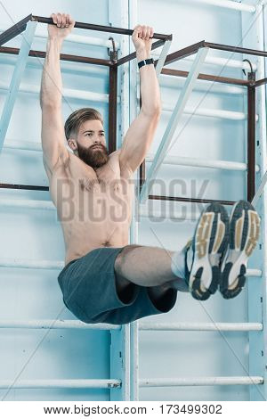 sporty shirtless man exercising on sport equipment in gym