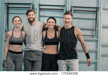 smiling sporty men and women in gym