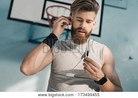 portrait of sporty man using earphones while training