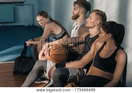 side view of sporty men and women sitting on bench in gym