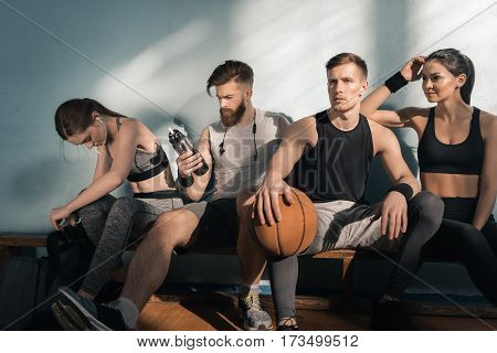 thoughtful sporty men and women sitting on bench in gym