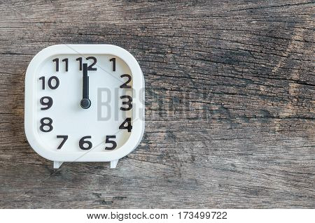 Closeup white clock for decorate in 12 o'clock on old wood floor textured background with copy space