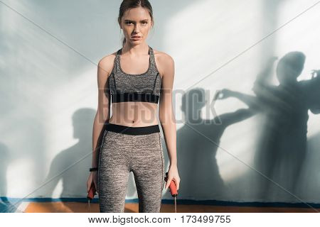 sporty young woman with skipping rope looking at camera