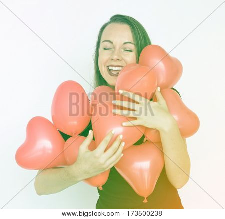 A caucasian woman is happy with a heart shape balloon.