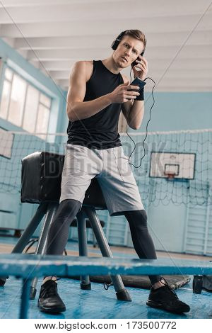 Athletic young man in headphones with smartphone leaning at pommel horse in gym