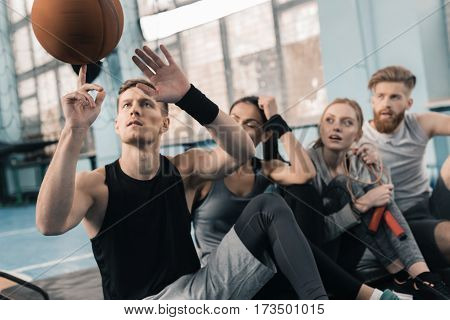 Surprised young sporty people looking at man balancing ball on finger