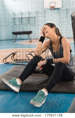 Attractive young sportswoman sitting on mat and laughing in sports hall