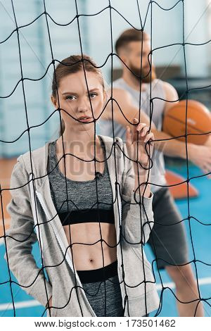 Young sporty woman looking at camera through volleyball net