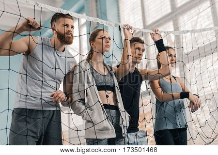 Sporty young people looking through volleyball net in sports hall