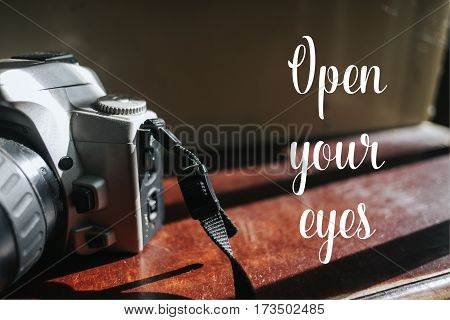 Isolated calligraphy on Camera film on brown wooden stairs. Quote about photo and photography. Open your eyes.