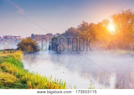 Fantastic foggy valley that glowing by sunlight. Unusual and picturesque scene. Location place Seret river, Ternopil. Ukraine, Europe. Retro filter. Instagram toning. Discover the world of beauty.