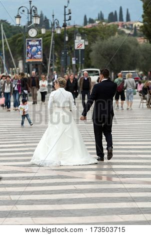 LAZISE ITALY - APRIL 30 2016: Bride and Groom walking on the promenade in Lazise on Lake Garda. Italy