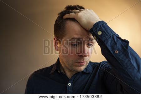 Young man in despair covers his head with hands. Worry due to problems and stress