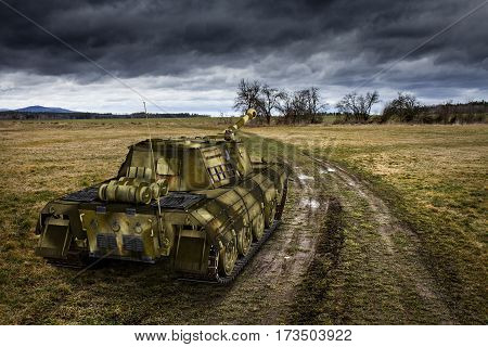 Army Tank On The Muddy Field Under The Dramatic Sky.