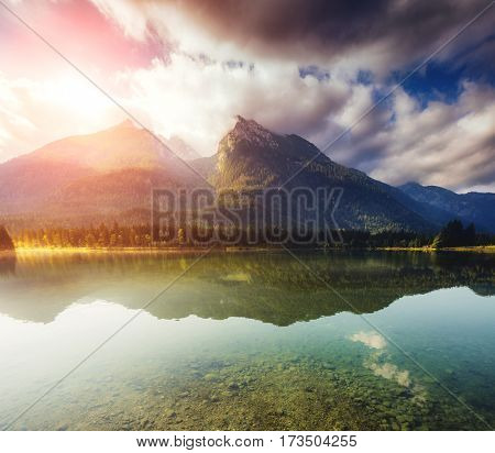 Great view of the famous alpine lake Hintersee that glowing by sunlight. Dramatic and picturesque scene.  Location resort National park Berchtesgadener Land, Upper Bavaria, Alps. Europe. Beauty world.