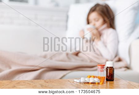 It will help to recover. Selective focus of medicines lyingon the table while little ill girl drinking tea and lying in bed in the background