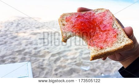 Hand Holding A Bite Toast With Strawberry Yam Beside The Sand Beach