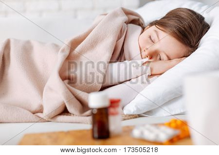 Sweet dreams. Pleasant tired little girl sleeping and resting at home while suffering from cold