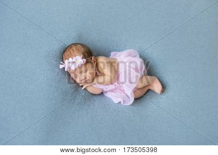 Sweet baby girl sleeping on her tummy, wearing pink little dress, in a flowery hairband