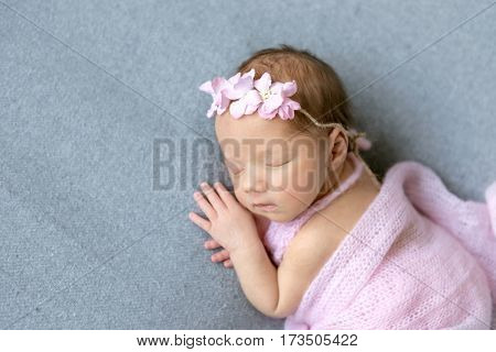 Adorable little girl napping on her side, dressed in a sweet pink dress, closeup
