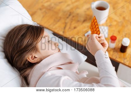 Take them regularly. Pleasant littlr girl taking medicines and lying in bed while resting in her bedroom