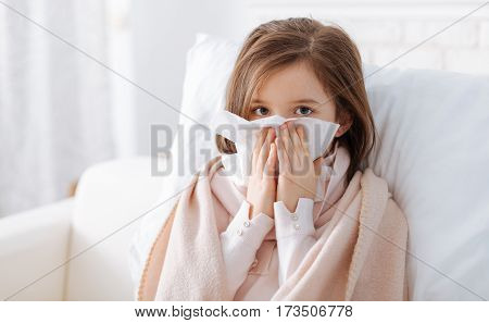 Combat your disease. Pleasant sick girl holding handkerchief and sitting on the couch while resting at home