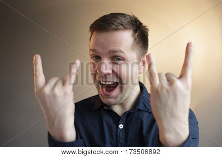 Man shows horns gesture. Fan of heavy metal music