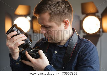 Young people change the lens on the camera. The professional photographer prepares for shooting in the studio.