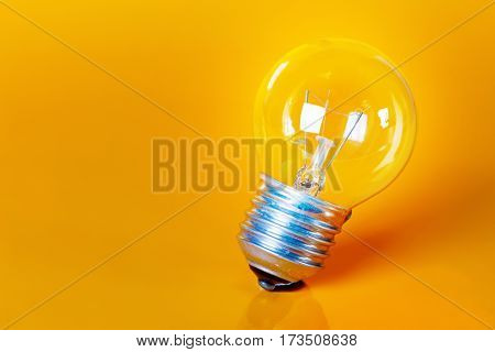 Clear Light Bulb on a Vivid Yellow Background