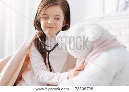 My first patient. Cheerful smiling llittle girl examinign her fluffy toy and pretending to be a doctor while resting at home