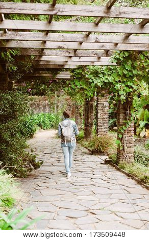 Girl with a backpack walking in a beautiful botanical garden in Porto, Portugal