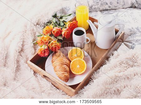 breakfast in bed with coffee croissant orange and juice