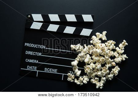 Clapperboard and popcorn on black background. Top view.