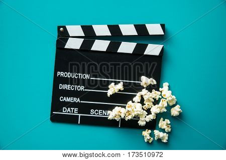 Clapperboard and popcorn on blue background. Top view.