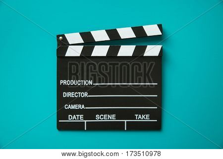 The vintage clapperboard on blue background. Top view.