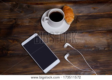 White Mobile Phone On Wooden Wooden Background With Headphones, Cup Of Coffee And Croissant