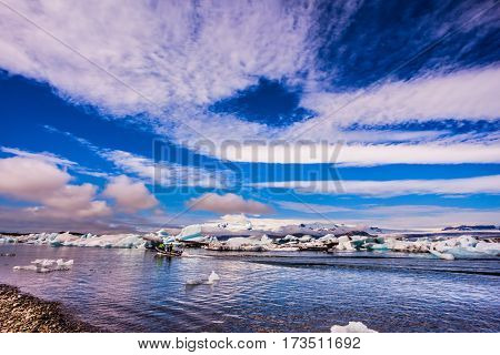 Clouds reflected in the water of lagoon. The concept of northern extreme tourism. The ice floes and cirrocumulus clouds of lagoon Jokulsarlon, Iceland