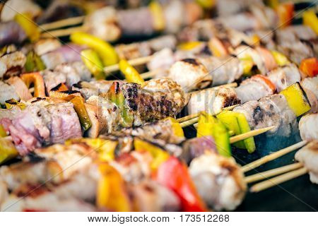 grilled skewers of different meat and vegetables on a hot grill