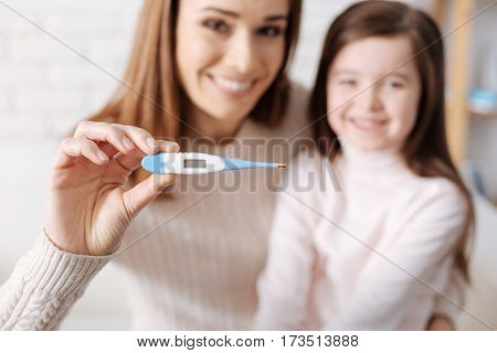 We did it. Selective focus of thermometer in hands of cheerful woman holding it and resting with her daughter
