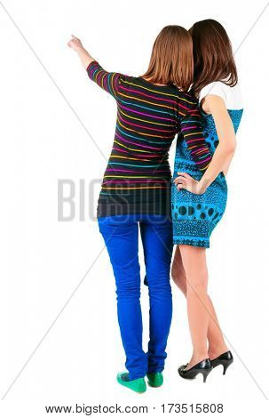 Back view of two young  brunette woman pointing at wall . beautiful girl friends  showing gesture. Rear view people collection.  backside view of person.  Isolated over white background.