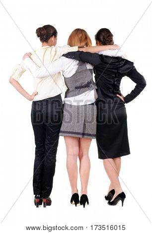 three beautiful young bussineswoman looking at wall. Rear view. Isolated over white.