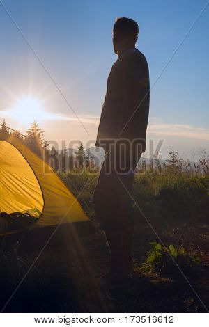 Traveler man stands next to a tent and admiring the beautiful sunset in the mountains. Carpathian Mountains Ukraine spring.