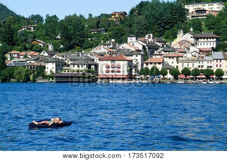 Man On An Inflatable Mattress Sunbathing In Front Of Orta