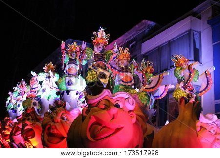 AALST, BELGIUM, FEBRUARY 26 2017: Unknown participants on one of the brightly lit floats during the annual carnival parade in Aalst, which is a UNESCO recognized event of Intangible Cultural Heritage.