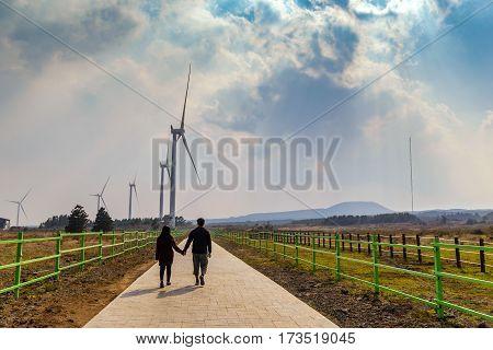 Lover hold hand at wind energy turbine farm, Jeju Island, South Korea