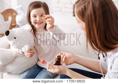 So bright. Overjoyed delighted little girl showing pill and going to take it while sitting on the couch with professional doctor